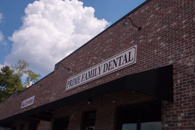 Prime Family Dental sign on brick facade, with blue sky in the background