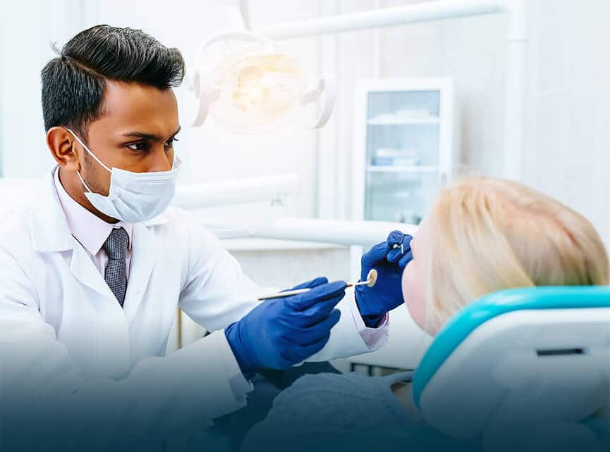 indian dentist helping patient
