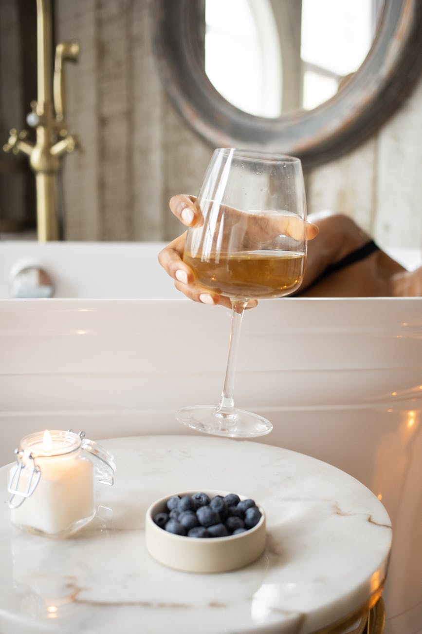 woman taking wineglass from round table in bathroom
