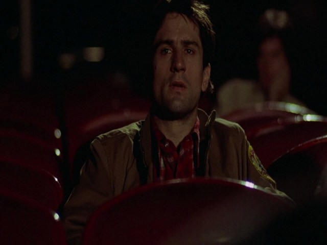 Robert De Niro sentado en una sala de cine en Taxi Driver de Martin Scorsese