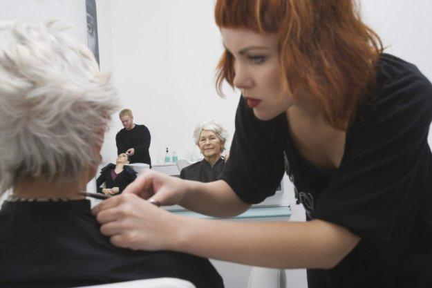 Female Stylist Giving Haircut To Senior Woman's Hair