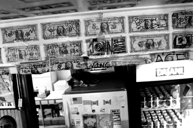 Dollars bearing messages adorn the wall and ceiling above a counter at Monk's Place, a Creeds institution. At bottom left, Ashley Johnson delivers an order. She has three dollars posted herself. [John-Henry Doucette/The Princess Anne Independent News]