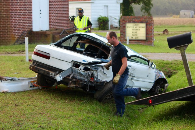 Lonnie Twiford, after righting a car that came to rest upside down in a crash, prepares to bring the vehicle aboard a Sandbridge Towing truck. In the background is Virginia Beach police Chaplain Albert Mentore, who assisted at the scene of the crash, in which three people were injured on Tuesday, Sept. 29, 2015. [John-Henry Doucette/The Princess Anne Independent News]