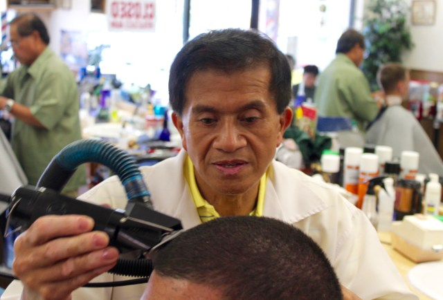 """Ernesto Castaneda, owner of Caste's Barber Shop, cuts the hair of Kieran Whitbold, 25, vacationing in Sandbridge from New England. When in the Beach, Whitbold said Caste's is his regular barber shop. """"I come here every summer,"""" he said. """"This place has the best haircuts in town."""""""