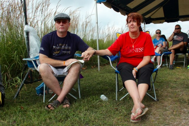 Steve and Kym Bach hold hands while names are read during a ceremony before the Out of the Darkness Community Walk at Mount Trashmore on Saturday, Sept. 12. The Bachs were among the speakers. [John-Henry Doucette/The Princess Anne Independent News]