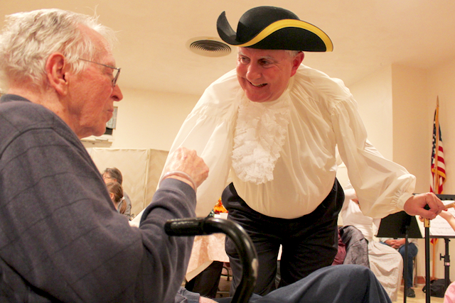 The Rev. Jack Davis, pastor of Tabernacle United Methodist Church, dressed appropriately for the church's annual Colonial Dinner, one of its major fundraising events that brings congregants together with the wider community at the historic church along Sandbridge Road in the Sigma area. Here, the pastor speaks with Stan Thurston of Atlantic Shores during the dinner on Saturday, Nov. 14. [John-Henry Doucette/The Princess Anne Independent News]