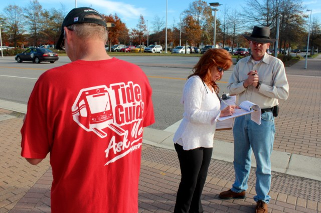 ► Reid Greenmun of Sawyer Lakes and Waverly Woods of Kempsville, with clipboard, were among those out and about collecting signatures for a petition seeking a light rail referendum next year. This effort asks a different question than the one proposed by City Councilmember Bob Dyer. The two collected signatures at the Virginia Beach Convention Center on Saturday, Nov. 21. Greenmun wore an old HRT shirt he bought in a thrift store. [John-Hernry Doucette/The Princess Anne Independent News]