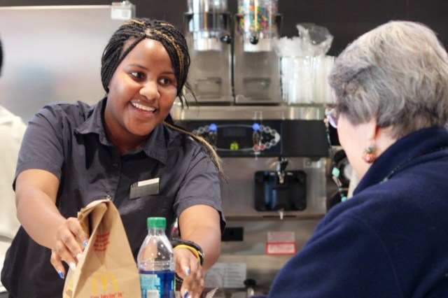 Mahala Hanson,19, hands a customer her order during the grand re-opening last month of the McDonald's location at General Booth Boulevard and London Bridge Road that was severely damaged by fire last summer. Hanson is a shift manager at the locally-owned restaurant. [John-Henry Doucette]