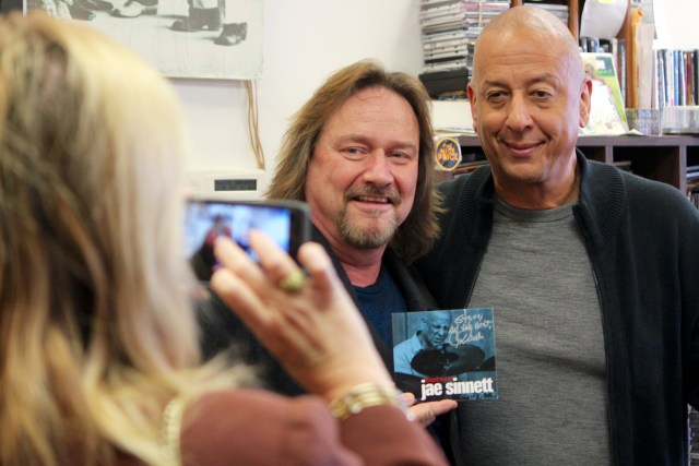 Musician Steve Archer poses with Jae Sinnett and an autographed copy of Zero to 60 while Steve Archer's wife, Sandy Archer, snaps a photo at Birdland Music. [John-Henry Doucette/The Princess Anne Independent News]