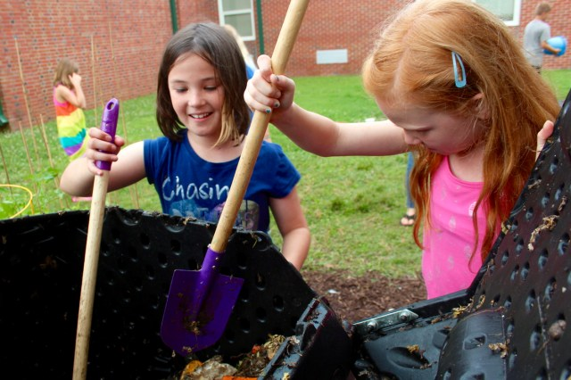 Maggie Kelley, 10, of Blackwater, and Zoey Walker, 9, of Pungo use shovels to break down organic matter in a compost tumble at Creeds Elementary School on Friday, June 17, 2016. [John-Henry Doucette/The Princess Anne Independent News]