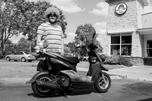 Josh Cantrell, 27, of Salem Lakes is seen with his Yamaha Zuma near Princess Anne Road and Tiffany Lane. He sports a wig on his helmet, which has gotten him pulled over. [John-Henry Doucette/The Princess Anne Independent News]