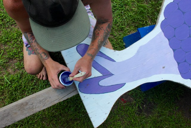 Farmhand Max Aaron, 24, of Red Mill, refreshes the paint on a sign at Pungo Blueberries, Etc., which recently opened for the summer season. [John-Henry Doucette/The Princess Anne Independent News]