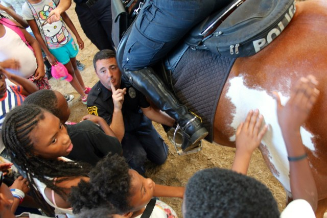 Campers from the Urban Summer Academy, a youth leadership development program, say hello to a horse at the Virginia Beach Police Mounted Patrol Unit barn in Pungo on Wednesday, July 20. Kneeling — and reminding the young people to speak softly and go with gentle touches — is Master Police Officer Aaron Dove. Officer Erica Slye is atop the horse. [John-Henry Doucette/The Princess Anne Independent News]