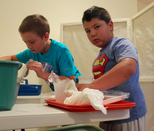 Andrew Stacy, 11, and Nic Windsor, 9, help bus tables. [John-Henry Doucette/The Princess Anne Independent News]