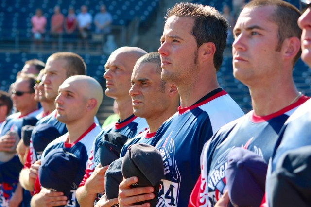 Virginia Beach firefighters playing for the Virginia Beach Professional Firefighters Local 2924 softball team stand together during the National Anthem before a charity game, the first Battle of the Bravest, against Chesapeake Firefighters at Harbor Park on Saturday, Aug. 27. The game raised money for the Muscular Dystrophy Association in conjunction with the recent Fill the Boot fundraising campaign. [John-Henry Doucette/The Princess Anne Independent News]