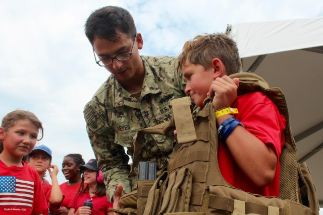 """The air show included opportunities for students to experience technology in action and interact with members of the armed forces. Above, Hunter Velzis, 9, of Salem Elementary School is helped out of heavy gear by Petty Officer 3rd Class Uriel Reyes, originally from Phoenix, after completing pushups. """"I can do that all day with a couple breaks for water,"""" Velzis said. Reyes is part of Construction Battalion Maintenance Unit 202 at Little Creek. [John-Henry Doucette/The Princess Anne Independent News]"""