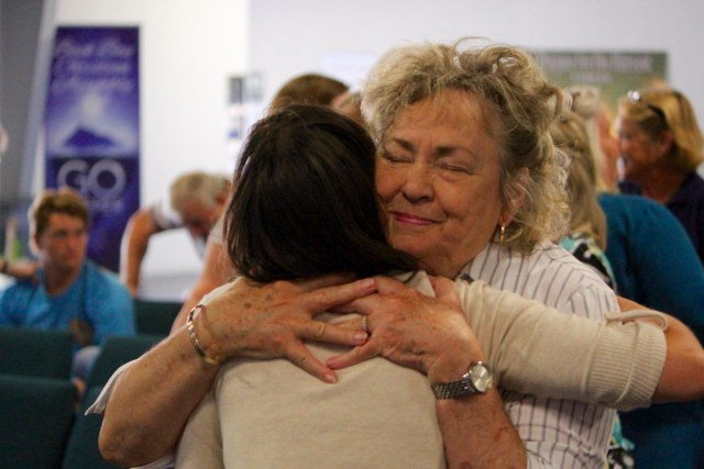 Linda Etheridge of Back Bay shares a hug with Samantha Walker of Knotts Island, N.C., during a service on Sunday, Sept. 11. [John-Henry Doucette/The Princess Anne Independent News]