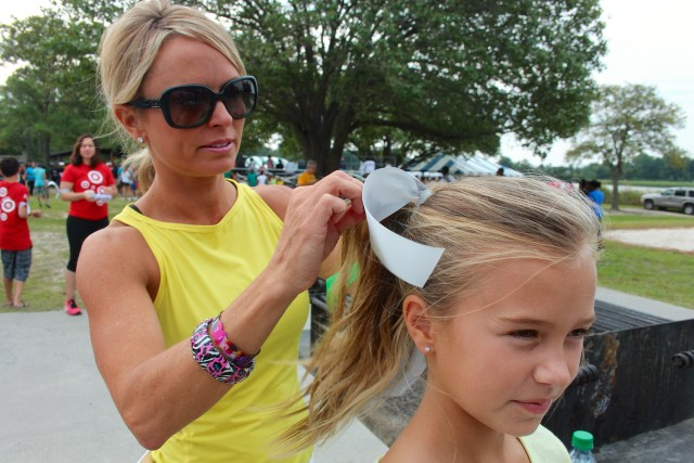 Tasha Frederick of Sandbridge ties a ribbon into the hair of Laney Frederick, 9. Ribbons of different colors raise awareness or are a remembrance of someone lost. [John-Henry Doucette/The Princess Anne Independent News]