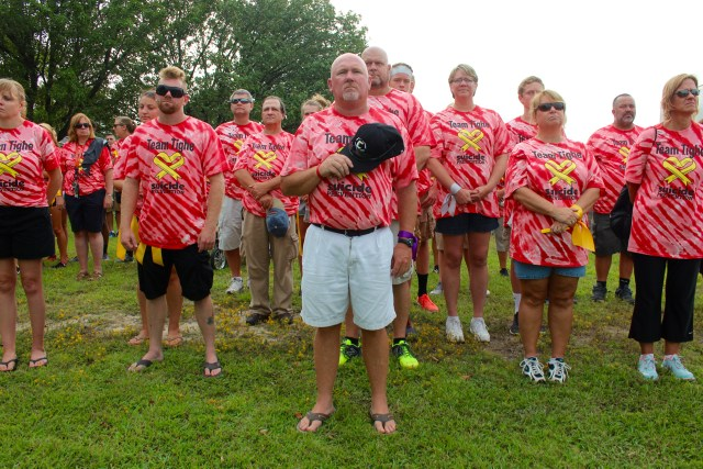 Denny Chalk, center, holds his cap over his heart during the National Anthem amid a ceremony before the walk. Team Tighe remembers Chalk's son, Tighe Chalk, who was 18 when he died this year. [John-Henry Doucette/The Princess Anne Independent News]