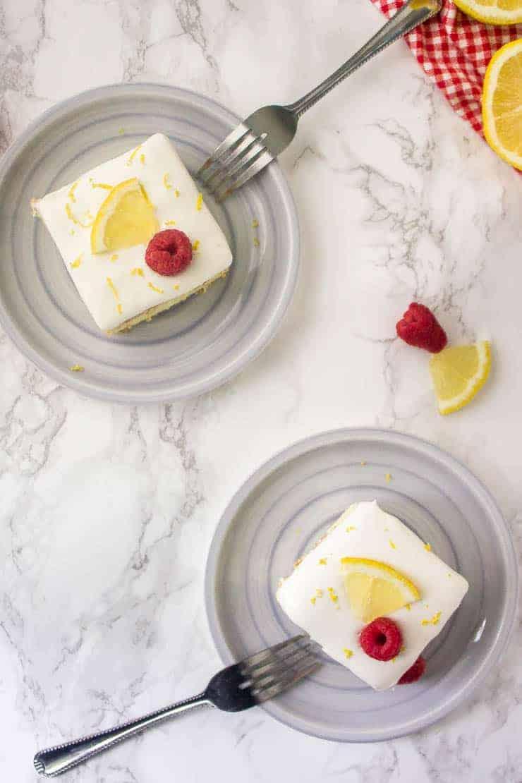 Lemon icebox cake on grey plates with raspberries and lemon