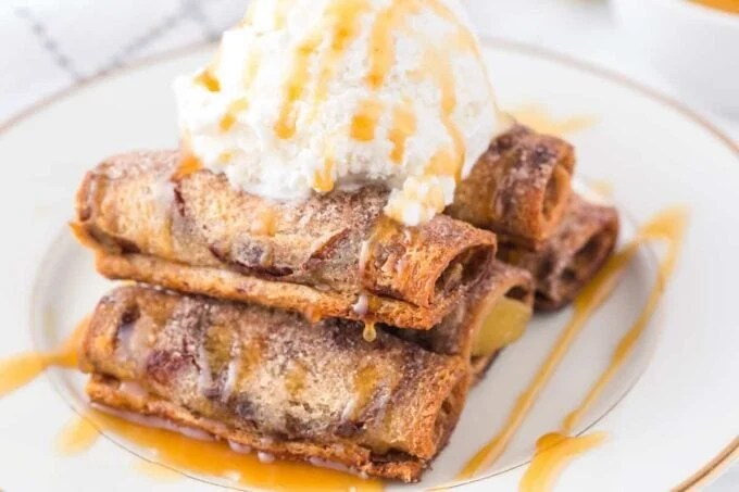 Roll up apple pie on a plate with a scoop of ice cream