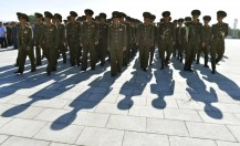 North Korean soldiers walk towards bronze statues of North Korea's late founder Kim Il Sung and late leader Kim Jong Il at Mansudae in Pyongyang