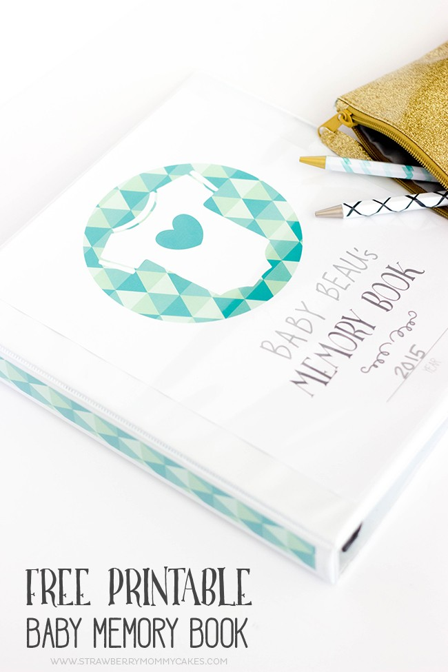 Closed blue baby memory book on white desk with pens