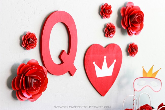 Red paper roses on white wall with red letter Q and red heart from how to make a paper rose post