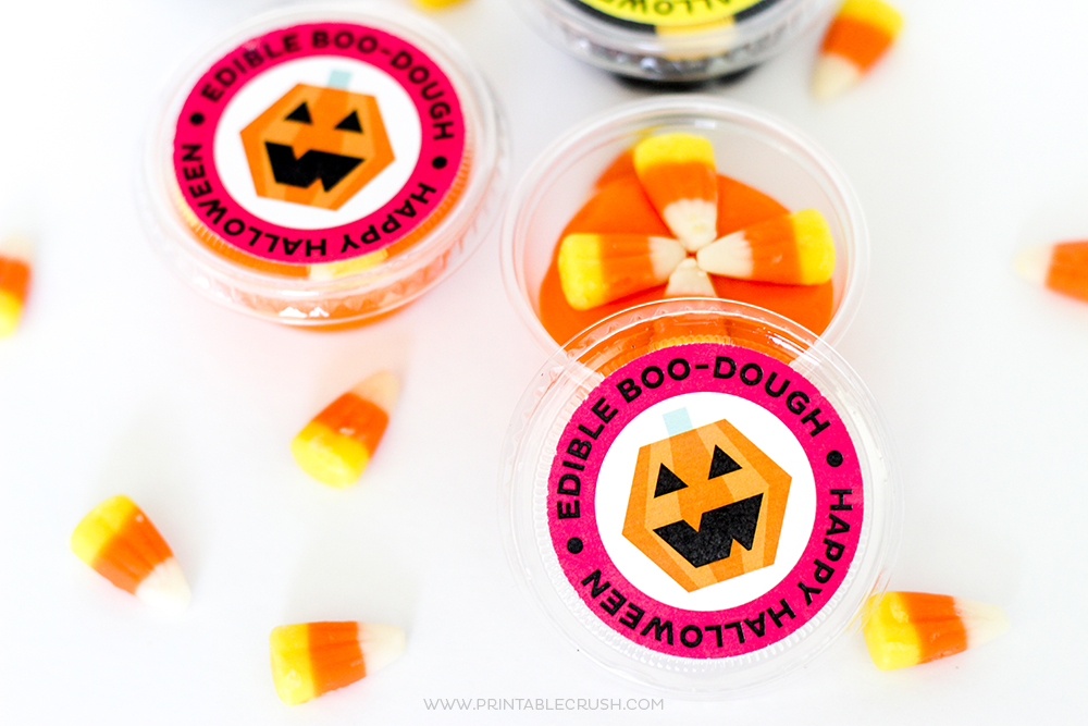 Orange edible play dough in clear container with candy corn on top