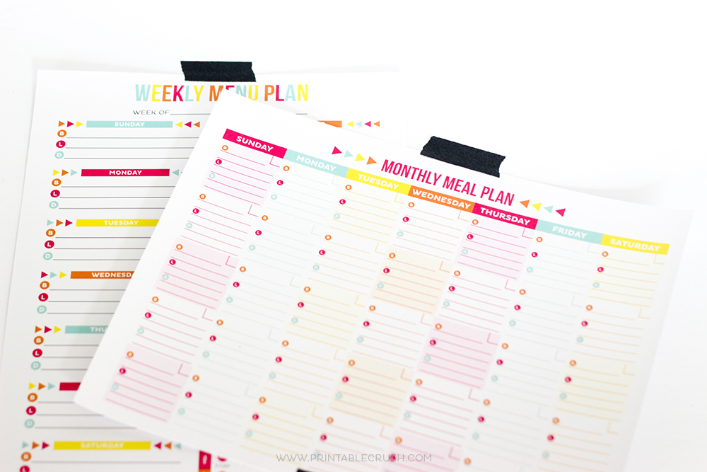 monthly meal plan sheets taped to wall with black washi tape
