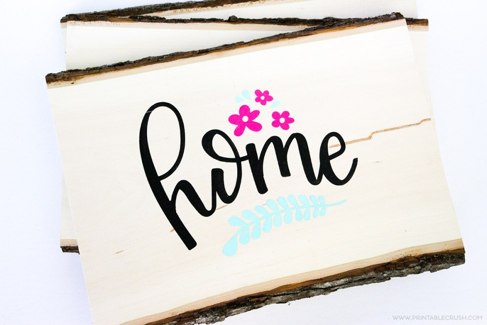 Piece of wood decorated with teal wording and pink flowers