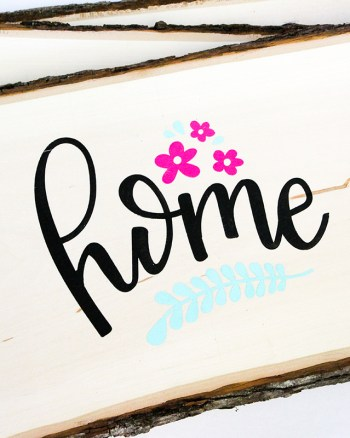 Wood sign with word home hand lettered on it