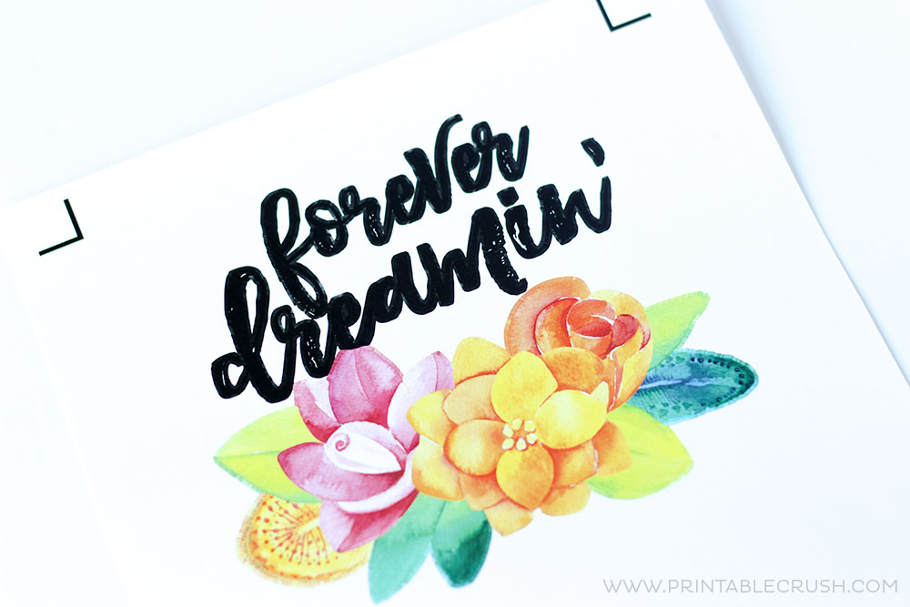 Colorful flowers and words 'forever dreamin' printed on white paper