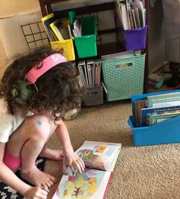 girl reading book on carpet