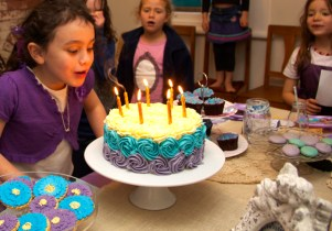 This is an image of the birthday girl blowing out the candles.