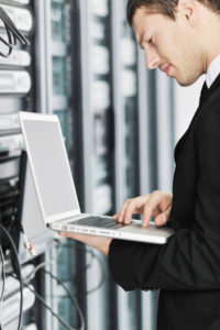 young it  engineer business man with thin modern aluminium laptop in network server room
