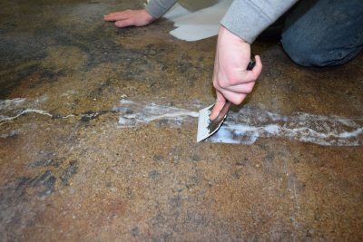 The flooring contractor repaired cracks by chasing them with a fast curing epoxy mortar. Courtesy of Covestro LLC.