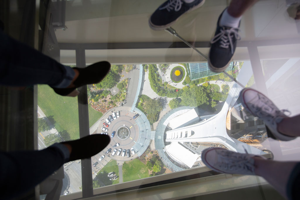 Guests step out onto Space Needle's The Loupe, a revolving glass floor. Courtesy of John Lok and Space Needle LLC