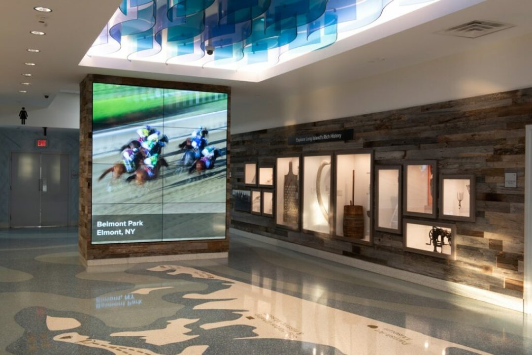 Common design features such as floor maps and artifact walls (shown here at the Long Island Welcome Center) create cohesive programming, while allowing the individuality of each region shine. Courtesy of Stantec