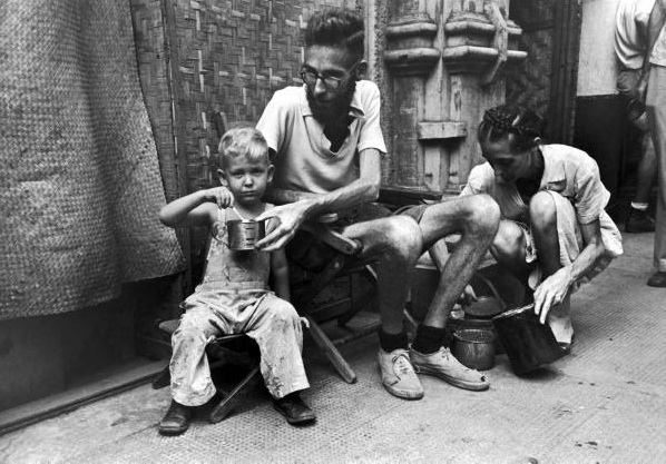 Carl Mydans. Emaciated father feeding Army rations to his son after he and his family were freed from a Japanese prison camp following the Allied liberation of the city. Manila, Luzon, Philippines. February 05, 1945