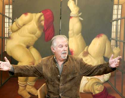 Colombian painter Fernando Botero gestures front of his new paintings depicting the horrors of U.S. guards' abuse of captives at Iraq's Abu Graib prison, Monday April 11, 2005 in Paris, France. Botero says he became so upset that he felt compelled to produce works showing his trademark chubby characters naked and being blooded by americans. (AP Photo/Francois Mori)