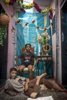 Alexia Webster, Two young friends pose for their portrait in a studio set up between houses in Dharvai, Mumbai. 2015