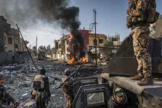 Iraqi special forces soldiers survey the aftermath of an ISIS suicide car bomb that managed to reach their lines in the Andalus neighbourhood of east...