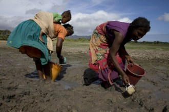 Women from drought-hit villages use small cups to gather silt-water lying in glutinous pools of mud – their drinking water for the day.