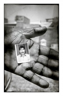 Pervaiz Massi hold the only remaining photograph of his brother, Ashraf Massi, at his grave side. He died while cleaning a sewer pipe in Bachwa...