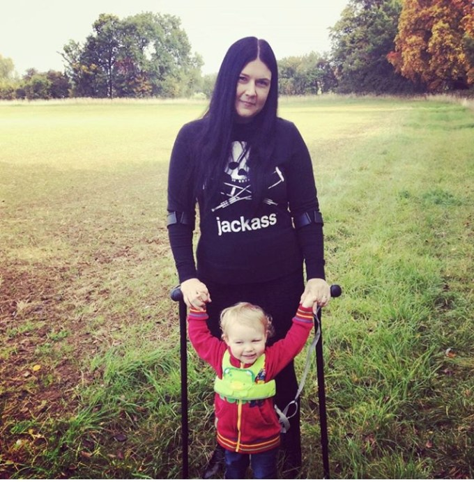 A picture of Kellie on her crutches with her son in a field.