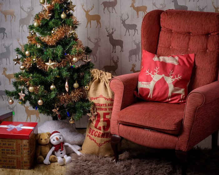A beautiful christmas scene with an armchair and presents in a sack.