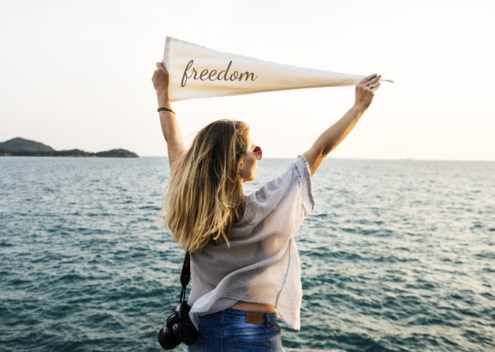"Lady standing in front of the ocean with a flag that has the word ""freedom"" written on it."