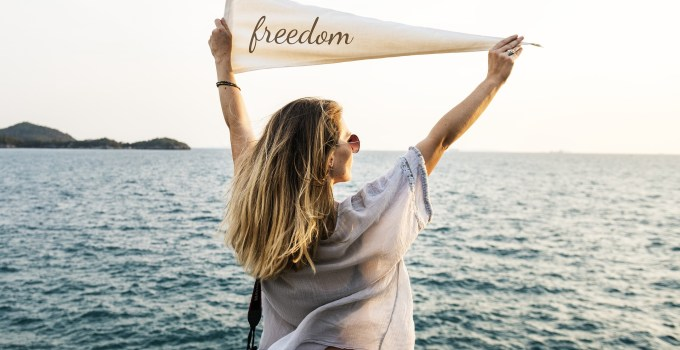 """Lady standing in front of the ocean with a flag that has the word """"freedom"""" written on it."""
