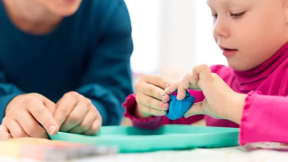 子どもに作業療法のゲームを教えている作業療法士